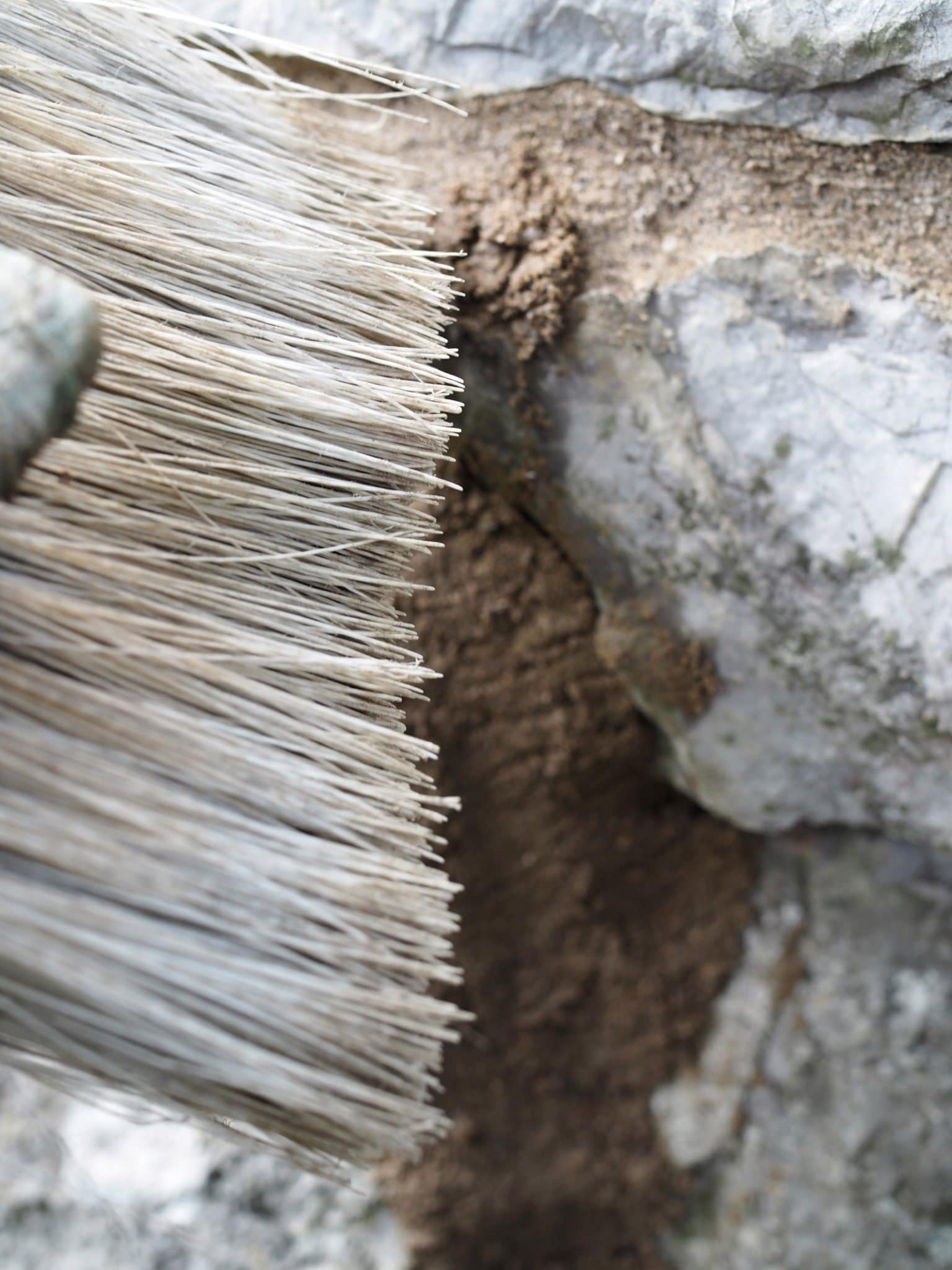 Brushing away excess mortar when repointing a stone wall