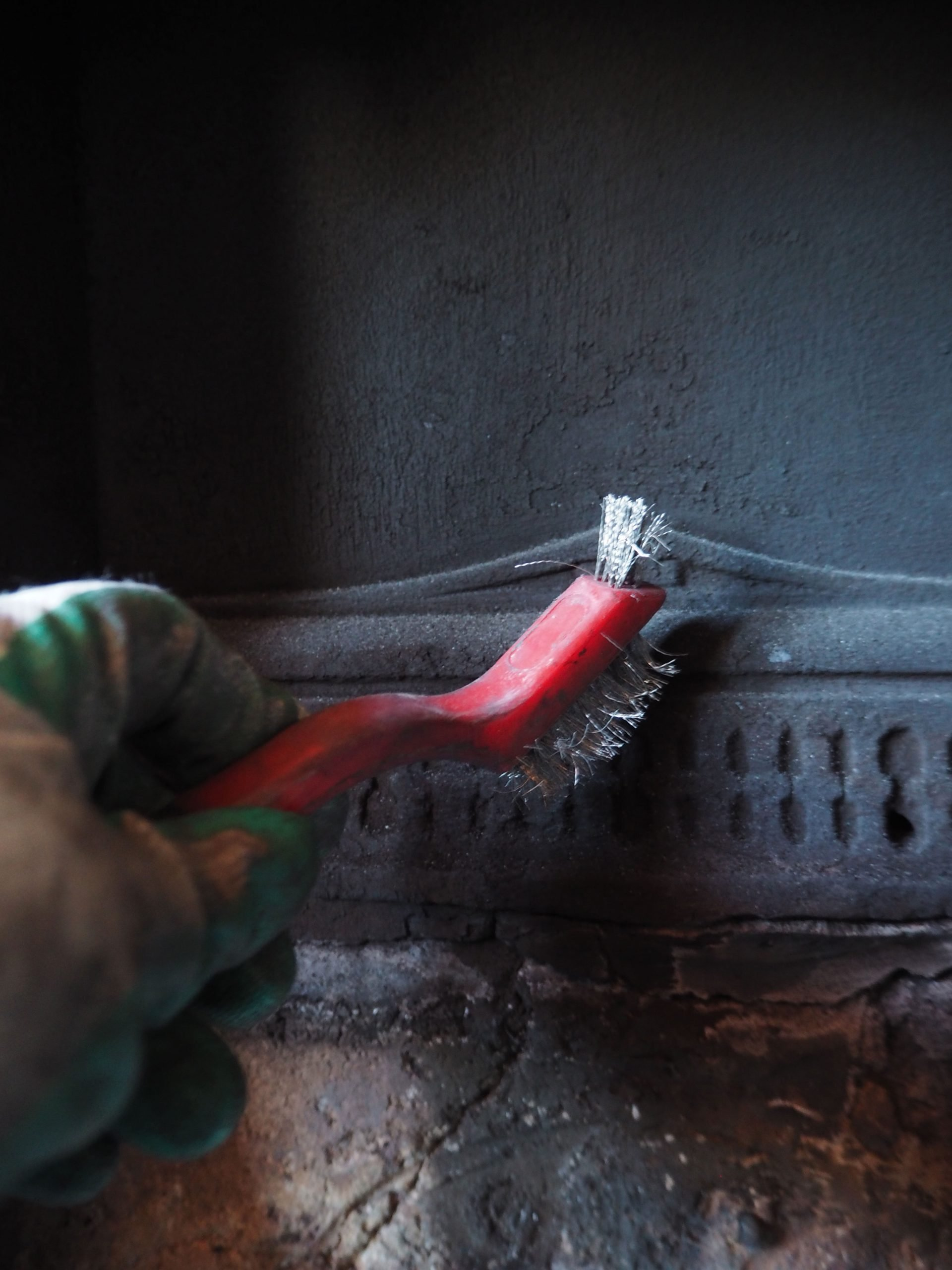 restoring a cast iron fireplace after winter - using a wire brush